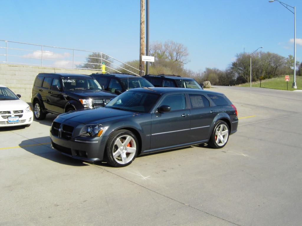 Blue Dodge Magnum SRT8 parked among other cars in the dealer lot