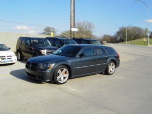 Blue Dodge Magnum SRT8 parked among other cars in the dealer lot